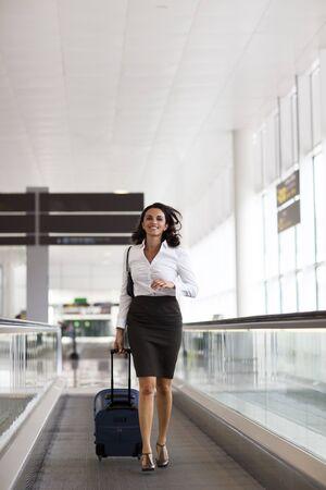 azafata: Mujer latina corriendo en el aeropuerto Foto de archivo