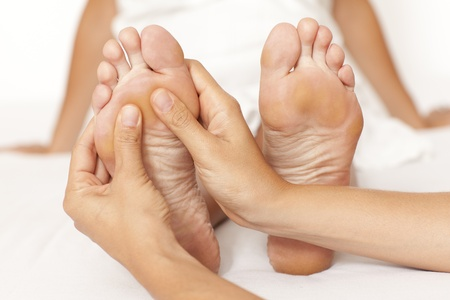 Human hands massaging a woman's foot photo
