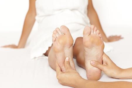 reflexologie plantaire: Les mains de l'homme masser un pied womans