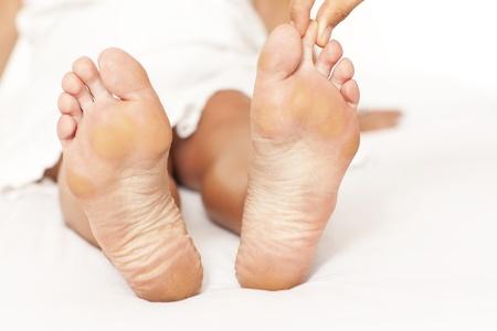 Human hands massaging a woman's toe photo