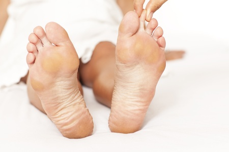 Human hands massaging a woman�s toe photo
