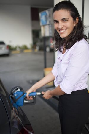 car gas: Woman filling gasoline inside the car in a gas station