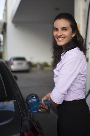 caras emociones: Mujer de llenado de gasolina en el interior del coche en una gasolinera