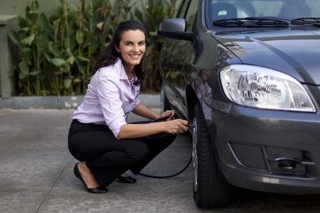 woman checking tire pressure photo