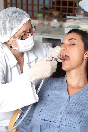 Hispanic woman receiving dental inspection from dentist photo