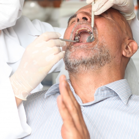 bad teeth: Older latin man having pain at the dentist Stock Photo