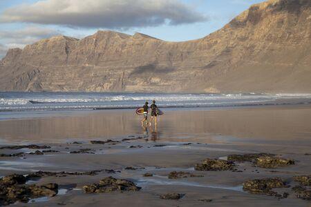 lanzarote: Two surfers walking on the surf beach Famara in Lanzarote