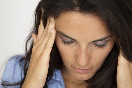 emotional pain: mujer latina que tiene dolor de cabeza