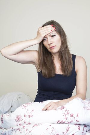 Young caucasian woman having headache sitting in bad Stock Photo - 12525617