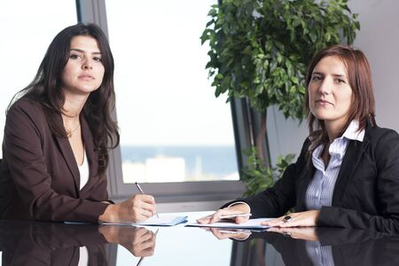 25 to 30: Two businesswomen sitting at office desk and negotiating
