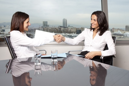 Shaking hands between two businesswomen photo