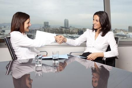 favorable: Shaking hands between two businesswomen Stock Photo
