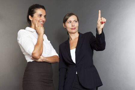 Two business women pointing on a virtual screen photo