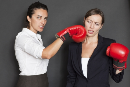 girl punch: businesswoman hits with red boxing glove Stock Photo