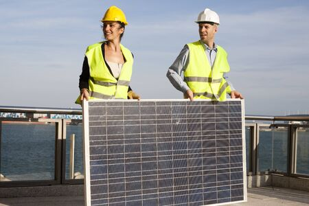 Engineers carry a solar panel photo