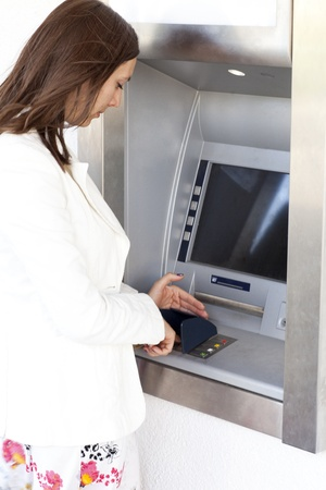 woman enters the PIN number at the ATM photo