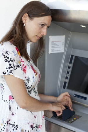 enters: woman enters the PIN number at the ATM Stock Photo