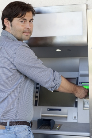 inserts: Man inserts card in the ATM