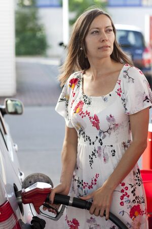refuel: Woman filling gasoline inside the car in a gas station