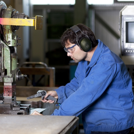 blue collar:  Handsome blue collar worker in factory   Stock Photo