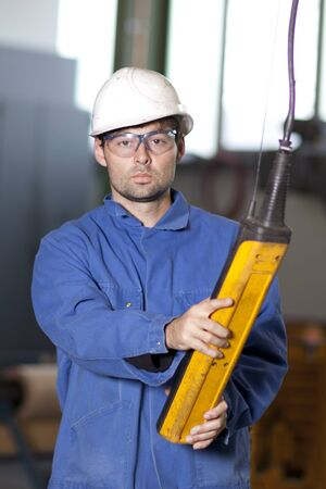 machinist: Blue collar worker using a crane in factory Stock Photo