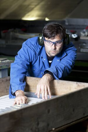 blue collar: Blue collar worker at machine in factory Stock Photo