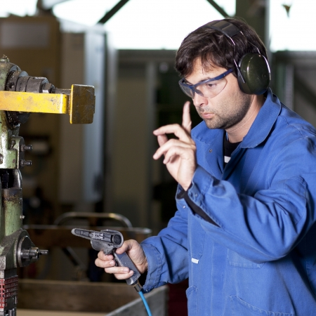 operate: Blue collar worker at machine in factory Stock Photo