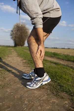muscle injury: Man touching his thigh during running because of pain Stock Photo