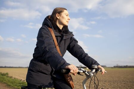 Woman riding a bike in autumn Stock Photo - 15277372