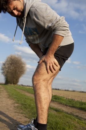 aching muscles: Man touching his thigh during running because of pain Stock Photo