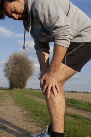 Man touching his thigh during running because of pain Stock Photo - 15277357