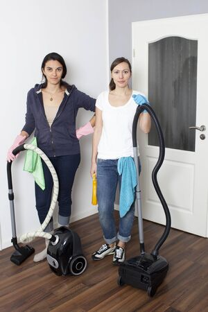 Two women vacuum a flat photo