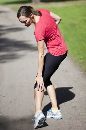 aching muscles: woman having cramp while running