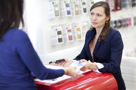 Femme d'acheter un smartphone avec de l'argent dans un magasin de téléphone cellulaire