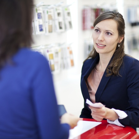 assistent: Woman buying a smartphone with cash in a cell phone shop Stock Photo