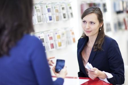 Woman choosing a phone in a cell phone shop Standard-Bild
