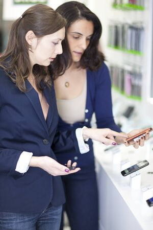 assistent: Shop assistant helping a customer choosing a smart phone  Stock Photo