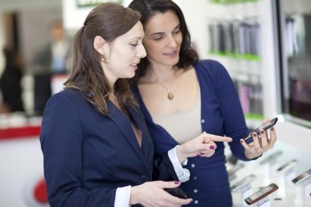 electronics store: Donna che la scelta di un telefono cellulare in un negozio di telefonia cellulare