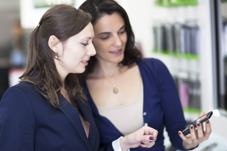Shop assistant helping a customer choosing a smart phone  Stock Photo