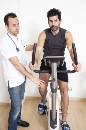 dark haired: Trainer helps man with spinning exercise