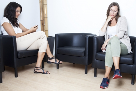 Two women waiting at doctor in waiting room photo