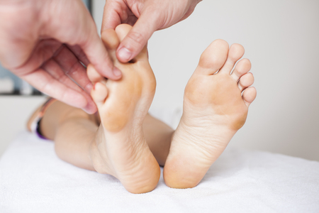 Human hands massaging a woman�s toe Stock Photo - 23365123