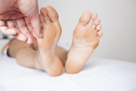 Human hands massaging a woman's toe Stock Photo - 23365124