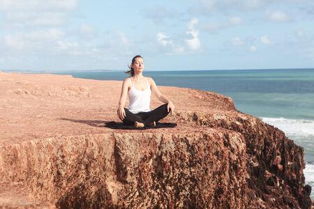 crosslegged: Yoga exercise sitting cross-legged on a cliff