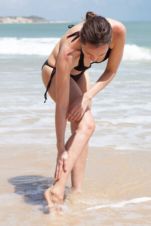 cramp: muscle cramp on the beach Stock Photo