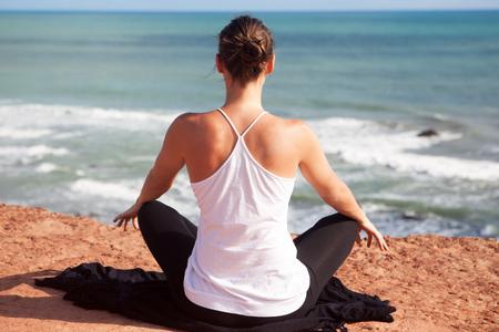 crosslegged: Yoga exercise sitting cross-legged rear view