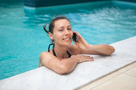Woman on the phone while relaxing in pool photo