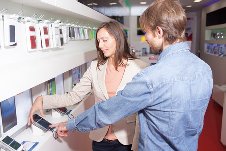 Choosing a phone in a cell phone shop Archivio Fotografico