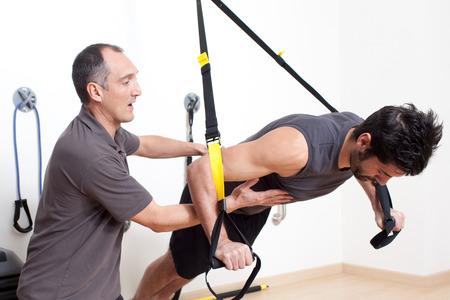 hombres haciendo ejercicio: entrenamiento de suspensión con el entrenador Foto de archivo