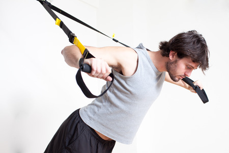 functional: muscular man making suspension training Stock Photo